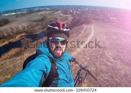 quick selfie young man on a bicycle outdoors, copy space for text or slogan - stock photo