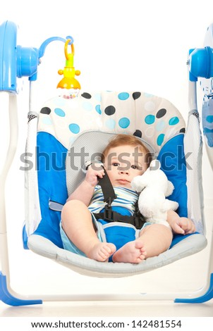 Quiet cute baby boy in a swing home against white background - stock photo