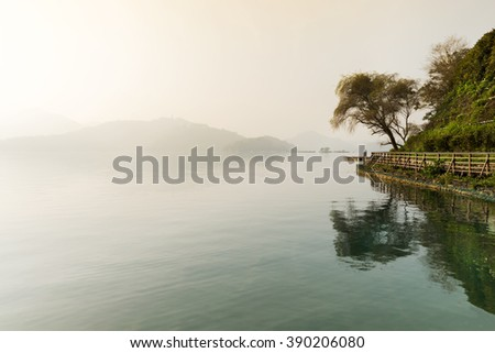 Quiet lake at dawn in the mist - stock photo