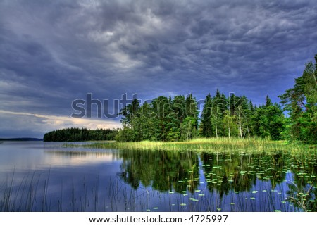 Quiet lake waiting for a thunderstorm - stock photo