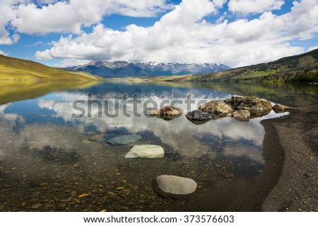 quiet mountain lake, reflection, blue sky and clouds, mountains. Chile, Patagonia, Torres del Paine Park, Laguna Azul