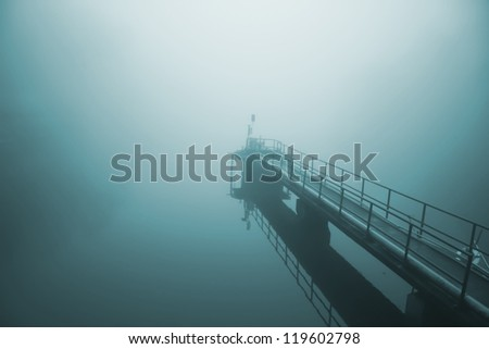 Quiet pier on a misty lake - stock photo