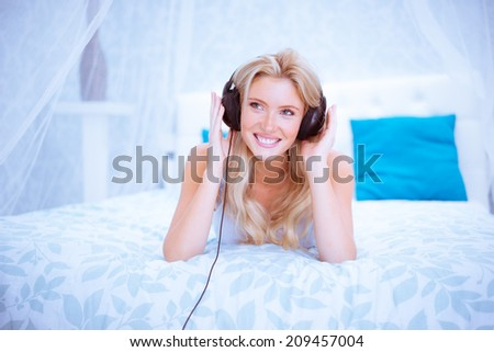 Quiet woman enjoying some music in her bedroom wearing headphones - stock photo