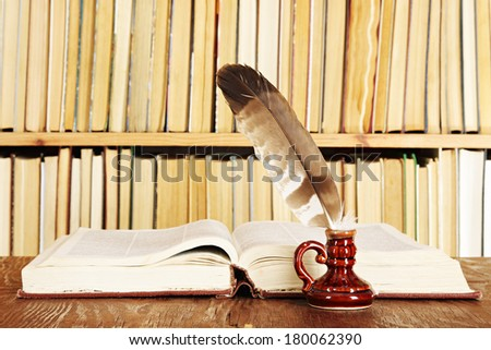 Quill in inkstand on a background of books - stock photo