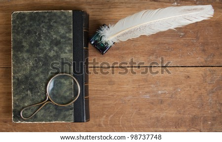 Quill ink pen and inkwell, old book and magnifying glass on wood table - stock photo