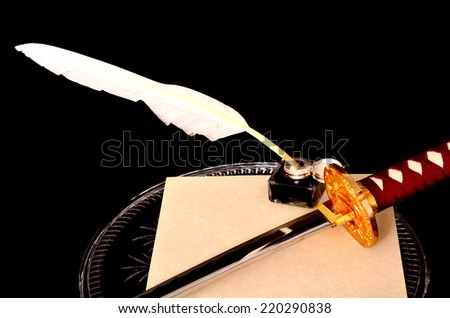 Quill parchment sword and ink well isolated over black - stock photo