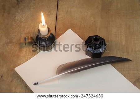 Quill  pen  and inkwell, and candlestick well resting on old paper. Literature concept - stock photo