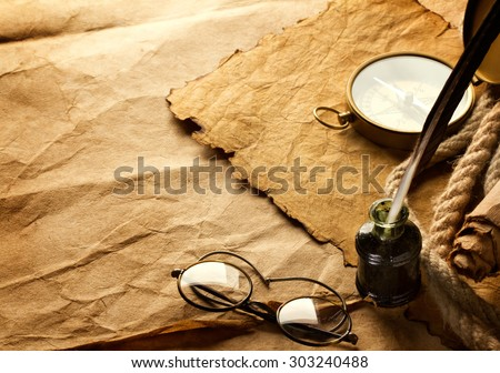 quill pen and vintage spectacles on paper background - stock photo
