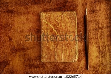 Quill pen near a vintage book. - stock photo