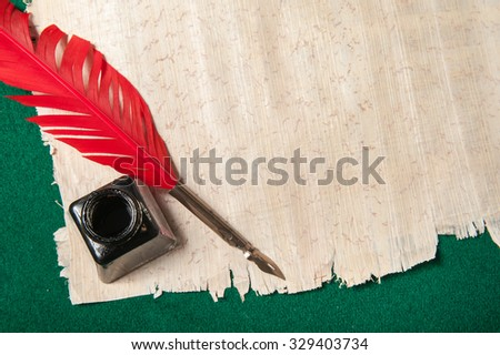 Quill pen on a papyrus sheet - stock photo