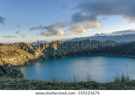 Quilotoa lake and andes range mountain against overcast cloudy background landscape scene, Ecuador