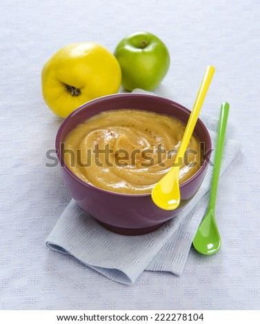 quince fruit puree apple in a bowl on a blue table cloth with colored spoons - stock photo