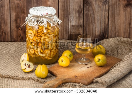 Quince fruits tincture and glass of drink on a burlap table setting. - stock photo