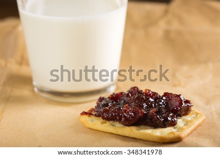 Quince jam on saltine cracker with one glass of milk on paper - stock photo