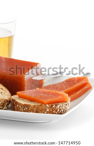 Quince jam slices on seeds bread on a plate over a white background. - stock photo