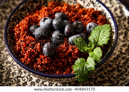 Quinoa blueberries and raspberries on a plate with black background pattern wood - stock photo
