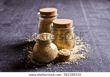 Quinoa dry seeds in a glass on a dark background. Selective focus. - stock photo