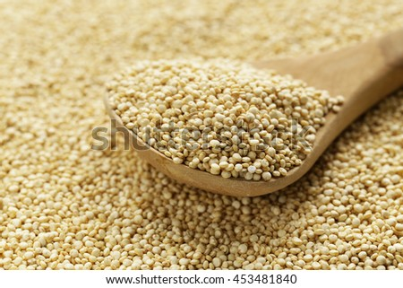 Quinoa grain in a wooden spoon close-up shot - stock photo