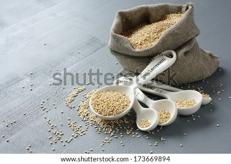Quinoa grain in small burlap sack and porcelain measuring spoons on gray background - stock photo