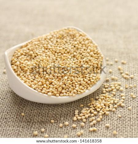 Quinoa grain in white ceramic bowl on sackcloth background - stock photo