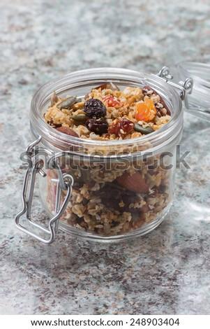 Quinoa granola in open glass jar on marble stone background  - stock photo