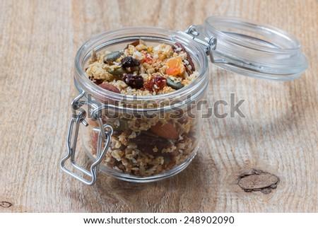 Quinoa granola in open glass jar on wooden background - stock photo
