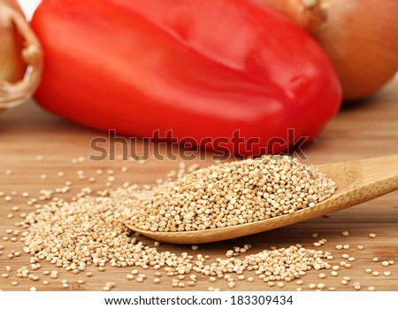 Quinoa on a wooden spoon, macro with selective focus.  Background of onions and a red pepper. - stock photo