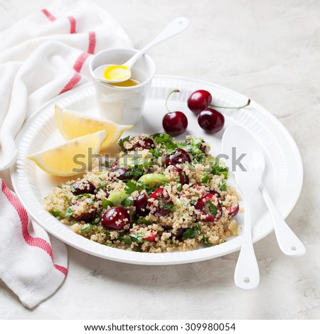 Quinoa salad with cherries, celery and cucumbers, selective focus - stock photo