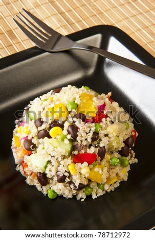 Quinoa salad with colorful vegetables on a black plate - stock photo