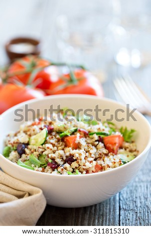 Quinoa salad with fresh tomatoes, cucumbers and salad leaves - stock photo