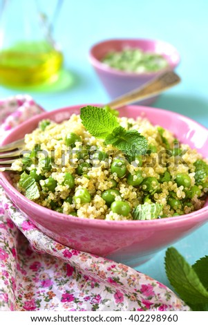 Quinoa salad with green pea and mint on a light  blue background. - stock photo
