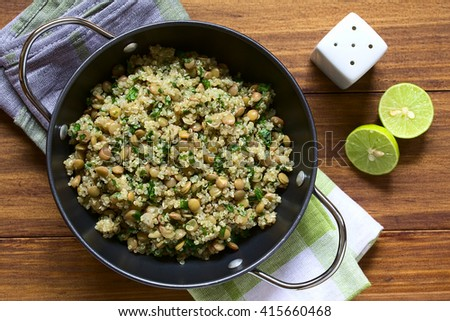 Quinoa salad with lentils and parsley in bowl, photographed overhead on wood with natural light (Selective Focus, Focus on the top of the salad)