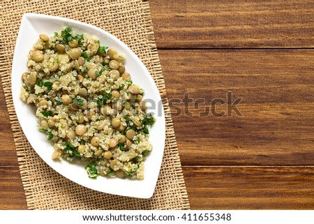 Quinoa salad with lentils and parsley on plate, photographed overhead on wood with natural light