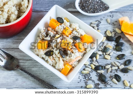 Quinoa salad with raw pumpkin, carrots and soy bean, Chia, pumpkin, sunflower and pine seeds, coconut sauce. - stock photo