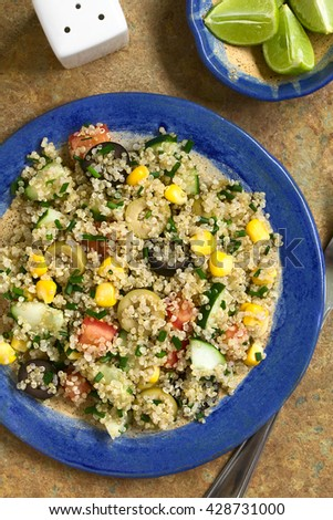 Quinoa salad with sweet corn, olive, tomato, cucumber and chives on plate, photographed overhead on slate with natural light - stock photo