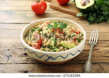 quinoa vegetarian salad avocado and tomato on rustic kitchen table - stock photo