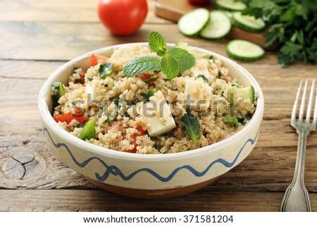quinoa vegetarian salad in ceramic bowl on rustic kitchen table - stock photo