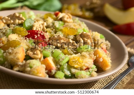Quinoa Waldorf Salad with apple, celery, yellow raisins and walnut served on plate, ingredients in the back, photographed with natural light (Selective Focus, Focus in the middle of the salad)