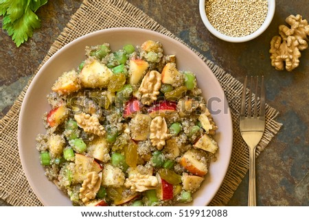 Quinoa Waldorf Salad with apple, celery, yellow raisins and walnut served on plate, photographed overhead on slate with natural light