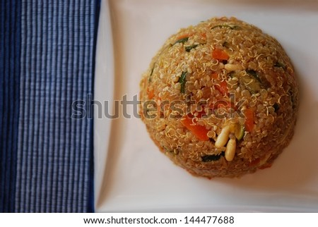 Quinoa with carrots, zucchini, onions and pine nuts in a white dish on a blue background - stock photo