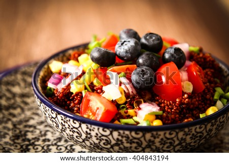 Quinoa with tomatoes chilli and corn on a plate with  black background pattern wood - stock photo
