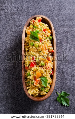 Quinoa with vegetables in a wooden plate on a dark background. Selective focus. - stock photo
