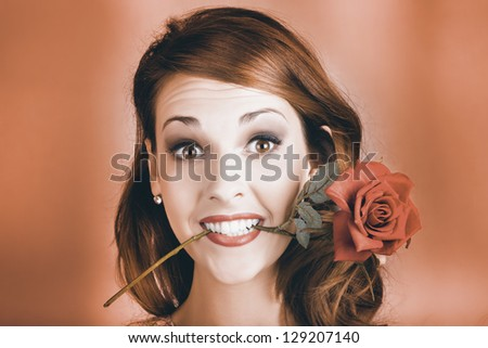 Quirky Face Portrait Of A Shocked Pinup Girl Wearing Vintage Makeup Holding A Red Rose In Mouth In A Valentines Day Gift Conceptual - stock photo