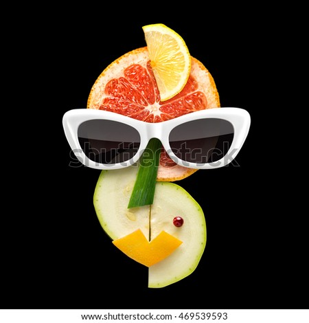 Quirky food concept of Picasso style female face in sunglasses made of fresh fruits on black background.