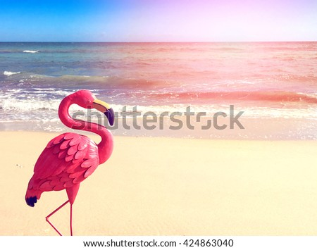 Quirky on-trend pink flamingo on a calm open beach for Summertime concept, with applied filters and lens flare.