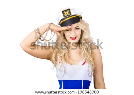 Quirky portrait of young beautiful sexy sailor girl with blond wavy hair and stylish make-up wearing sea admirals hat. Eye eye captain  - stock photo