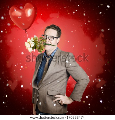 Quirky valentine portrait of a happy romantic man holding flowers in mouth with red love heart balloon. Gift of romance - stock photo