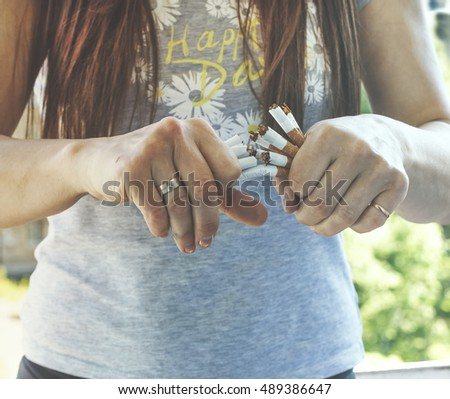 Quit smoking cigarettes. A young girl breaks a cigarette