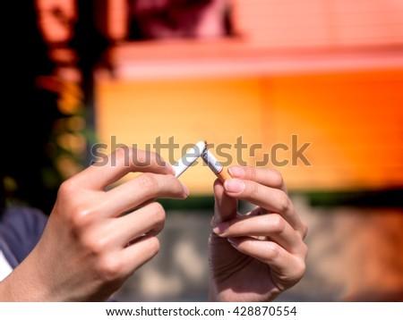 Quit smoking - female hand crushing cigarette - stock photo