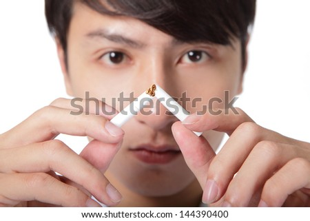 Quit smoking, man hands breaking the cigarette, close up, asian model - stock photo